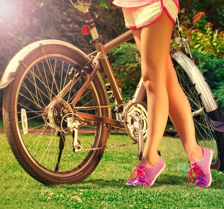 animal leg: young  girlwith bike in the park on a sunny summer day Stock Photo