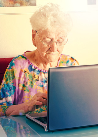 mature woman using computer for communication photo