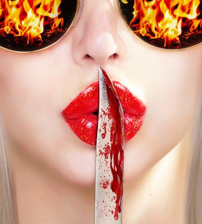 frenzy: bloody knife on lips. secrecy Stock Photo