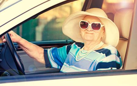 gelukkig senior vrouw in zonnebril en hoed rijden auto. Stockfoto