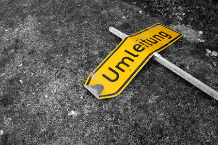 Damaged yellow sign Detour on monochrome background Stock Photo