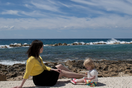 mammy: Outdoor portrait of beautiful blonde mother and her cute daughter. Small girl and her mammy looking at the sea. Summer sunny day. Happy holiday together.