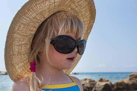 Toddler girl looks in Audrey Hepburn - style glasses on holiday
