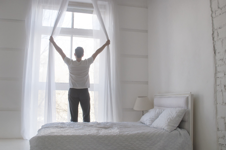 jalousie: Young man opening curtains to welcomw morning and light, rear view, white