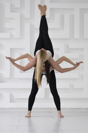 Two young girls practicing acro yoga balance pose, black sportswear, white abstract background