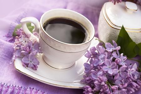 磁器のカップのコーヒーとライラック