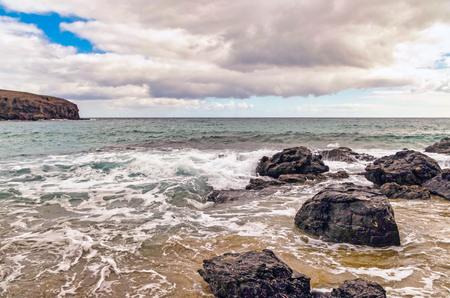 Scenic view of rocks in sea against sky. Photo taken on Playa Puerto Muelas, a public beach on Lanzarote, Las Palmas, Spain. 版權商用圖片