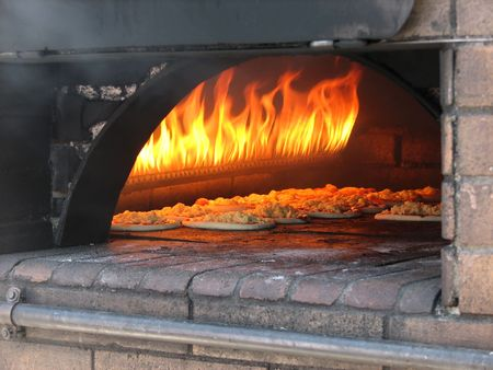 pizza prepares in old stove near fire Standard-Bild