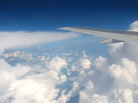 airplane wing above clouds and horizon photo