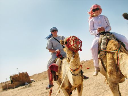 extreme heat: people traveling on camels in egypt desert Stock Photo
