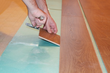 worker installing new laminate flooring  photo