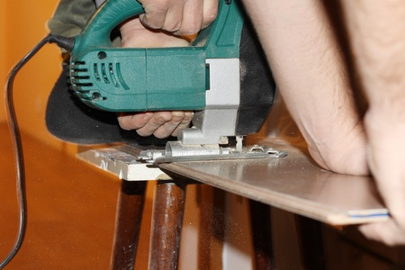 jigsaw, electric saw cutting plank photo