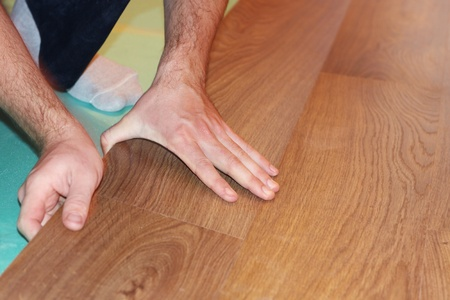 worker installing new laminate flooring photo