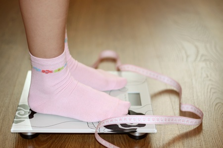 Woman on scale with pink tape measure, diet photo