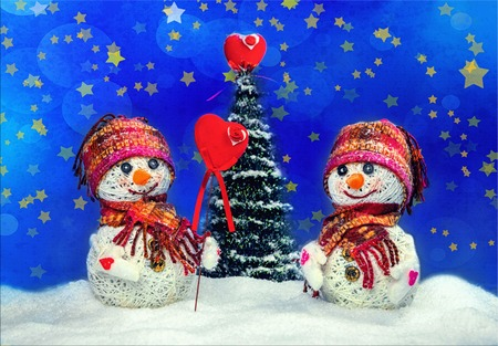 Love snowmen. Snowfall. Snow background. Love concept. Valentines Day Greeting card with copy-space. Snowmen love couple set against each other on Christmas background