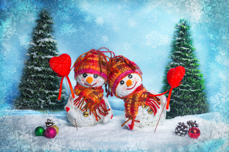 snowmen. postcard to the day of the holy valentine. snowmen with a heart on a background with Christmas trees, snow falls
