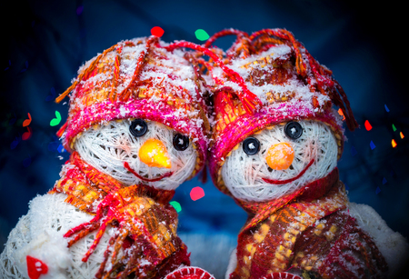 snowmen. postcard to the day of the holy valentine. snowmen with a heart on a dark background with colored garlands