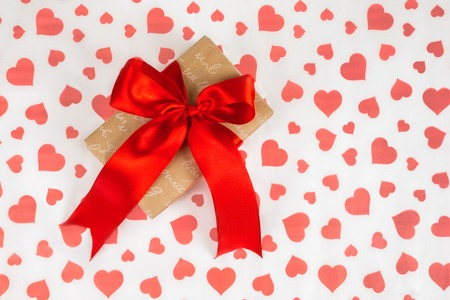 Valentine's Day or a romantic event. Presented as a red ribbon on a white paper with red hearts