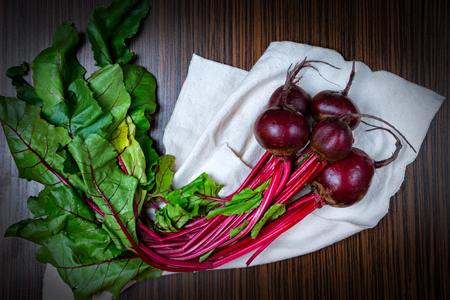beets on the table, along with vegetables, onions, tomatoes garlic, on wooden table background