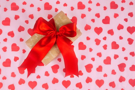 Valentines Day. Presented as a red ribbon on a pink paper with red hearts Stock Photo