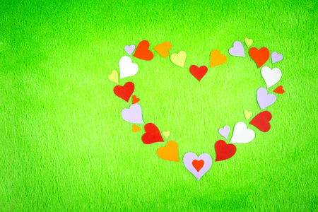 colored paper hearts in the shape of a heart on a green cloth