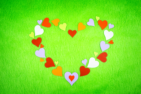 colored paper hearts on a green cloth Stock Photo