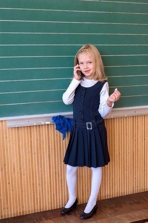 First grade pupil a girl writing on green blackboard at school lesson 스톡 콘텐츠