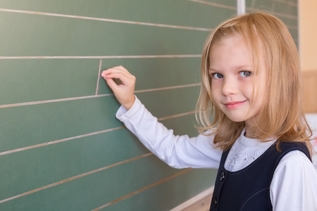 First grade pupil a girl writing on green blackboard at school lesson Stock Photo