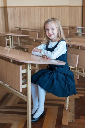girl in the first grade, is sitting at the desk