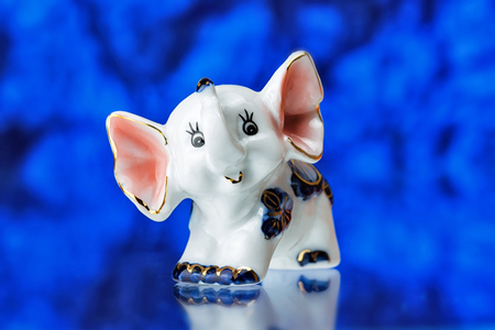 porcelain statuette of the elephant on a blue background,