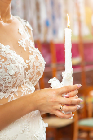 Bride and groom holding the candles. Close up.