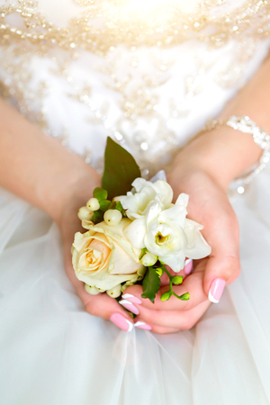 Brides hands with a bouquet for the groom.