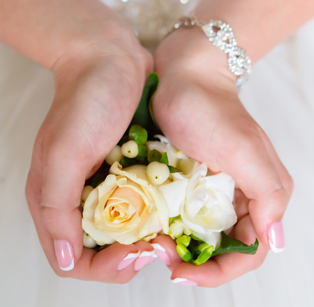 Bride's hands with a bouquet for the groom. Stock fotó