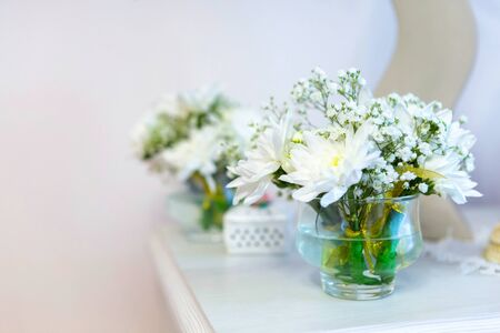 beautiful flowers, white chrysanthemums in weight on the fireplace,