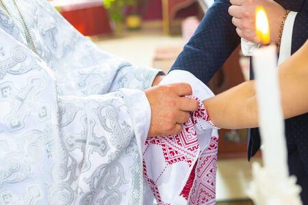 traditional Christian Wedding. the priest tied his hands to the newlyweds with a wedding towel on church. Imagens
