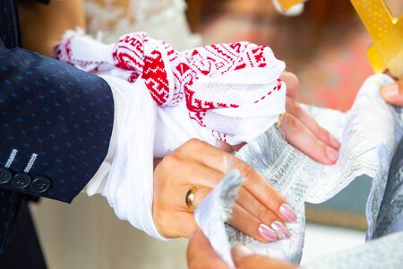 traditional Christian Wedding. the priest tied his hands to the newlyweds with a wedding towel on church. 스톡 콘텐츠