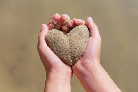 childrens hands hold the heart out of the sand, summer, love concept. place for text