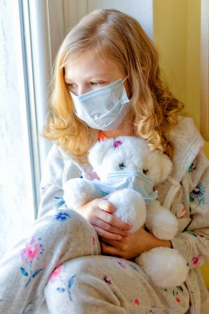 girl in medical mask with teddy bear, looking out the window, quarantine coronavirus. sick children