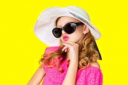 beautiful little girl in a pink dress, sunglasses and hat from the sun on a bright flat background, baby emotions, place for text Фото со стока