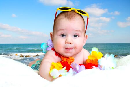 smiling baby boy in Hawaiian wreath and beach hat. baby on sea background. place for text