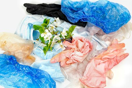 used gloves, medical masks and shoe covers. The problem of ecology and recycling of medical waste. protection against coronavirus, covid-19 and other viruses and infections. green branch of fresh blossom on a pile of garbage Фото со стока