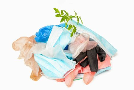 used gloves, medical masks and shoe covers. The problem of ecology and recycling of medical waste. protection against coronavirus, covid-19 and other viruses and infections. green branch on a pile of garbage Фото со стока
