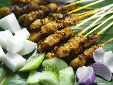 Malaysia food-Satay,ketupat,cucumbers and onions on a banana leaf