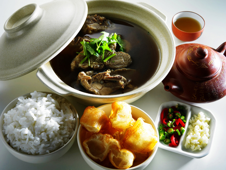 Malaysia food-Bah kut teh,a teapot of chinese tea,a cup of chinese tea,A bowl of chopped yau char kway,a bowl of rice,chillies and garlic Reklamní fotografie