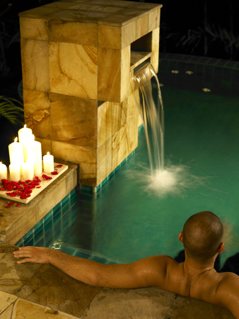 Man relaxing in the pool with lit candles by the poolside Stockfoto
