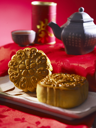 moon cake with tea pot on red background