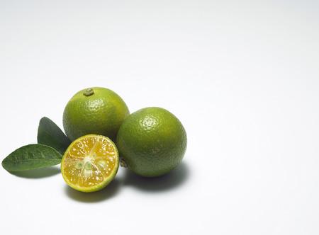 Trois citrons verts, entiers et coupés en deux