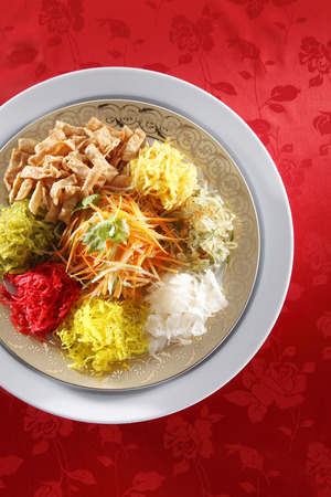 yusheng  on red texture background with copyspace Archivio Fotografico