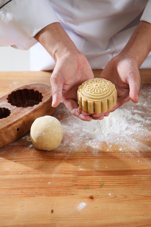 chef holding a mooncake ready for bake