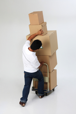 delivery man struggling to carry moving boxes.